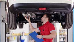 mechanic servicing a car on a hoist