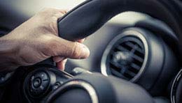 close up of a hand holding a steering wheel